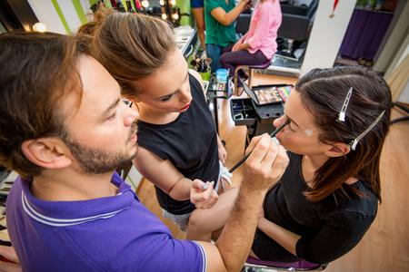 Makeup teacher helping students training to become makeup artist