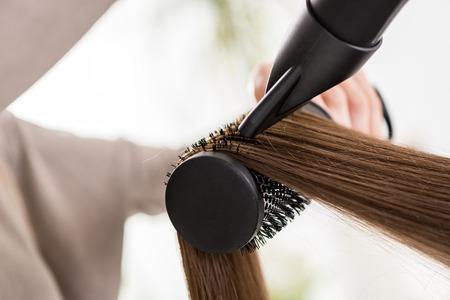 secador de pelo: Primer plano de un cabello marr�n secado con secador y cepillo redondo.