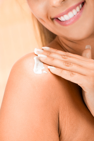 unrecognizable person: Beautiful young woman applying body lotion. Close up. Unrecognizable person.