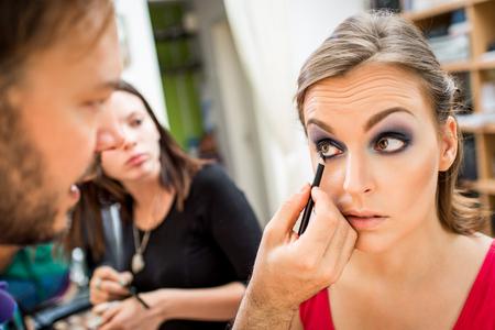 levantandose: Cierre plano de un hombre maquillador conseguir delineador para modelar.