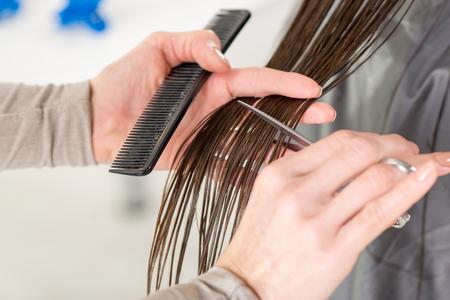 capelli LISCI: Primo piano di un parrucchiere tagliare i capelli di una donna.