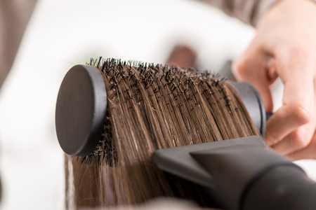 secador de pelo: Close-up of a drying brown hair with hair dryer and round brush. Foto de archivo