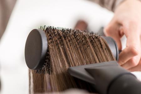 hair dryer: Primer plano de un cabello marr�n secado con secador y cepillo redondo.