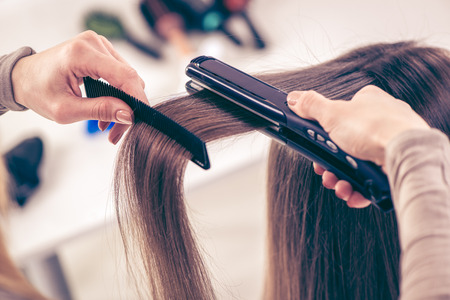 long hair woman: Close-up of a hairdresser straightening long brown hair with hair irons.