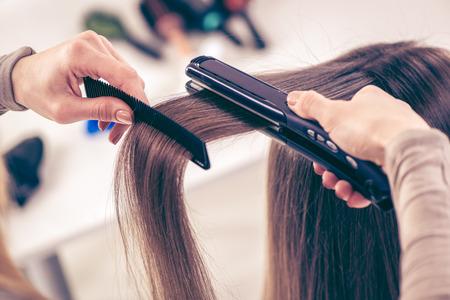 capelli lisci: Primo piano di un parrucchiere raddrizzare i capelli lunghi castani con ferri dei capelli.