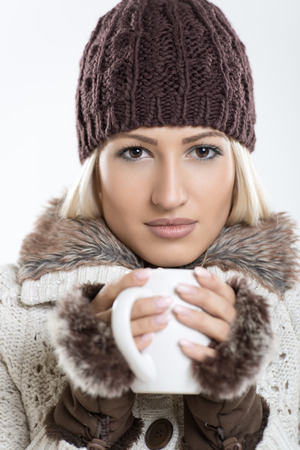 Portrait of young beautiful girl in winter clothes, holding a cup of hot tea in her hands and looking at camera. Stock Photo