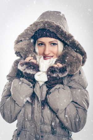 Beautiful girl in winter jacket with fur hood while snowing. Looking at the camera. Stock Photo