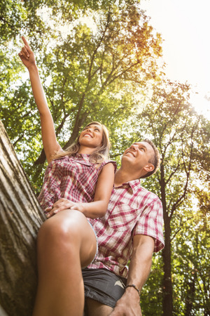 Beautiful young couple sitting on fallen tree in the forest and enjoying. Girlfriend pointing with finger far away. Stock Photo