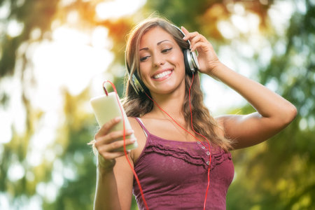 Happy beautiful girl in the park and listening music from smart phone. Stock Photo