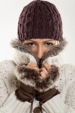 ropa de invierno: Chica joven hermosa en ropa de invierno con un gorro de lana y guantes de piel, se pega al cuello de piel en la que se metiendo. Mirando a la c�mara.