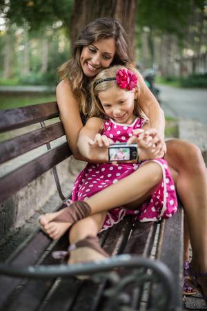 familias unidas: Feliz linda niña y su madre posando para un autorretrato en el banco en el parque.