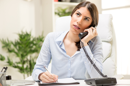 phoning: A young thinking businesswoman phoning in office