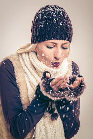 ropa de invierno: Close-up de la hermosa mujer joven en ropa de invierno, ya que sopla copos de nieve que sostiene en sus manos.