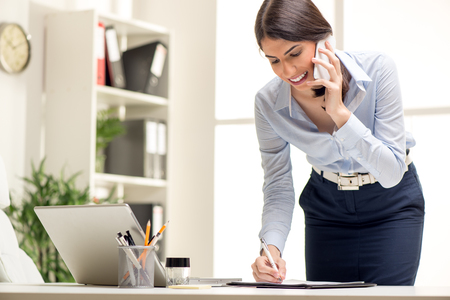 secretary phone: Beautiful Busy Businesswoman, standing in office, writing in planner and talking on mobile phone. Stock Photo