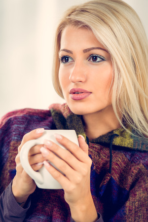 Beautiful blonde girl sits tucked, thinking and holding a cup of tea.