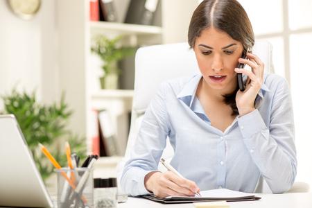 persona pensando: Una joven empresaria pensamiento llamando con el tel�fono inteligente en el cargo. Foto de archivo