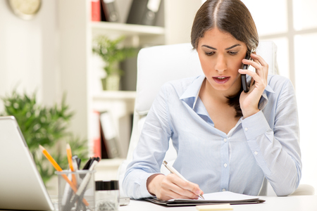A young thinking businesswoman phoning with smart phone in office.