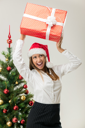 wearing santa hat: Beautiful young businesswoman wearing santa hat and holding Christmas gifts. Stock Photo