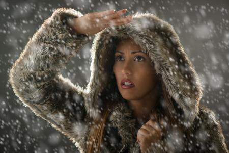 ropa de invierno: Retrato de una mujer joven en ropa de invierno preocupado mirando a trav�s de la nieve lejos. Foto de archivo