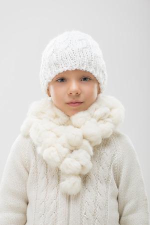 ropa de invierno: Retrato de una ni�a linda en ropa de invierno blanco. Mirando a la c�mara. Foto de archivo