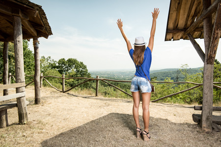 raised viewpoint: Cheerful woman on summer travel vacation standing by viewpoint with arms raised. Rear view. Stock Photo