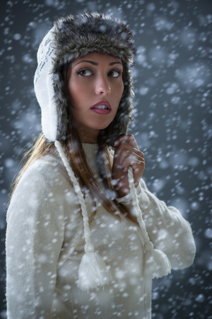 cold season: Portrait of a beautiful young woman in winter clothes at snow. Stock Photo