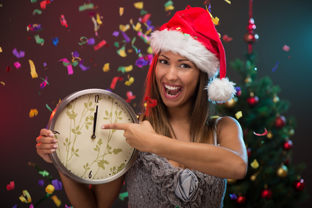 12 o'clock: Cheerful beautiful woman celebrating New Year and showing midnight on the clock. She is having fun, confetti is in the air. Stock Photo