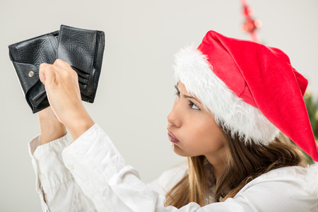 empty wallet: Young beautiful businesswoman wearing santa hat and looks worried at empty wallet.