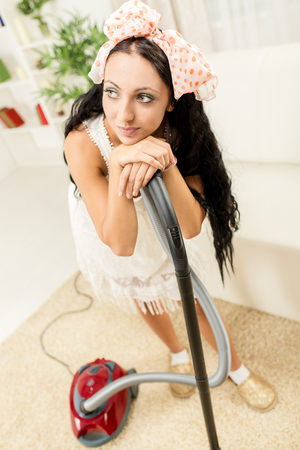 carpet clean: A young housewife standing leaning on vacuum cleaner tired of housework. Stock Photo