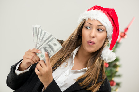 Successful businesswoman wearing santa hat and holding money.