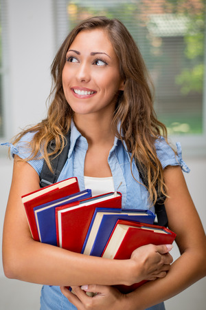 beautiful teen: Happy beautiful teenage girl with Colorful books and school bag. Stock Photo