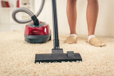 carpet clean: Woman vacuuming the house. Close-up with vacuum cleaner.
