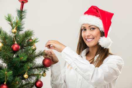 decorating christmas tree: Portrait of a beautiful young businesswoman wearing santa hat and decorating Christmas tree.