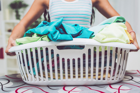 Close-up of a woman hands is holding basket laundry for ironing