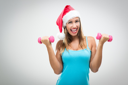 woman with camera: Beautiful fitness woman wearing santa hat doing exercise training arms lifting dumbbells.