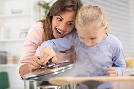 chicas guapas: Madre hermosa joven y su hija lindo cocinar comida saludable en la cocina.
