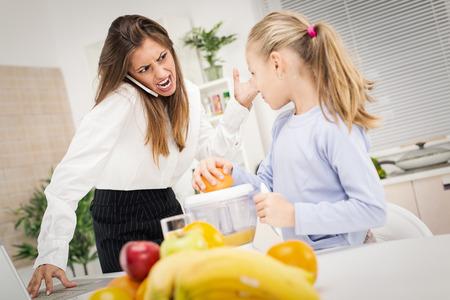 enojo: Madre con exceso de trabajo que acomete a su hija por la mañana para ir más rápido porque tarde al trabajo. Ellos enojarse con los demás a causa del estrés. Foto de archivo