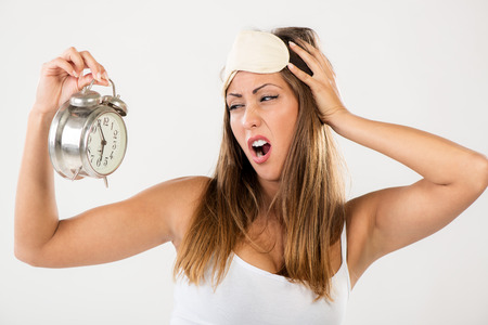 tired woman: Beautiful young woman holding alarm clock. She is tired and lazy in morning. Stock Photo