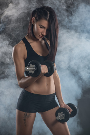 strengthen: Attractive muscular young woman doing exercise to strengthen biceps with dumbbells on dark background.