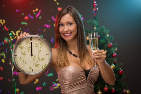12 o'clock: Happiness beautiful woman celebrating New Year. She is showing midnight on the clock and toasting with champagne. Confetti is the air.