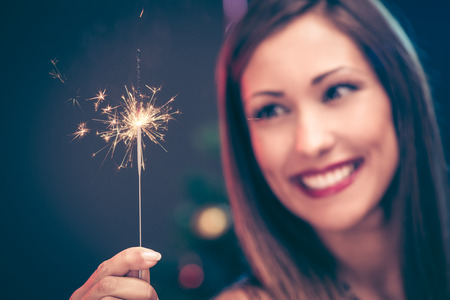 Close-up of a beautiful woman holding with sparkler. Focus on foreground, on sparkler.