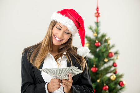 wearing santa hat: Successful businesswoman wearing santa hat and holding money.