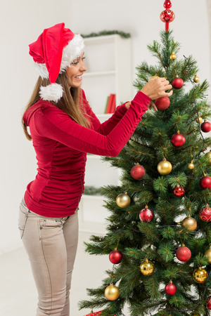 decorating christmas tree: Happy beautiful young woman decorating christmas tree with red ornament at home.