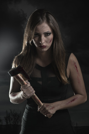 axe girl: Beautiful dangerous girl with rusty axe. Looking at camera. Stock Photo