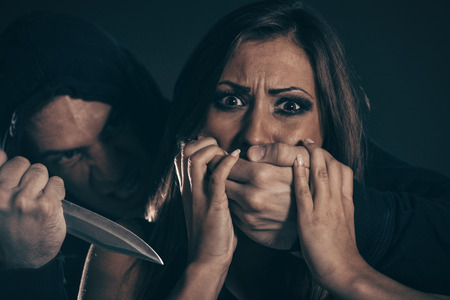 abuser: Young woman abuse victim with mans abuser with knife and his hands on her mouth. Stock Photo
