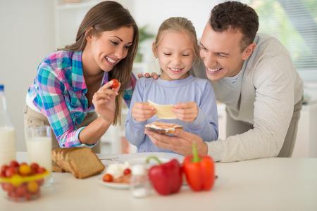 Hermosa familia alegre disfrutando mientras se prepara el desayuno en la cocina.