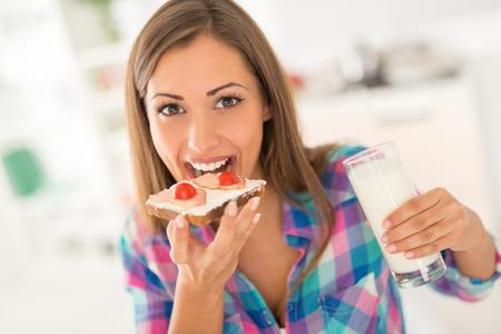 bocadillo: Joven y bella mujer tomando el desayuno en la cocina doméstica. Ella está comiendo sándwich fresco y leche de consumo. Mirando a la cámara.