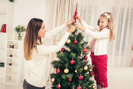 Young mother and her daughter decorating Christmas tree at home. Stock Photo