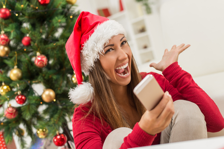 Cheerful young woman wearing Santa's hat is holding a smart phone at Christmas Time.