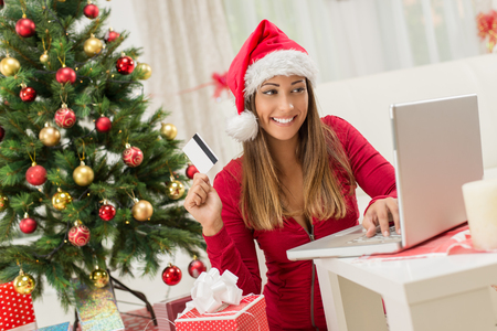 lady shopping: Cheerful young woman wearing Santas hat is buying Christmas presents online at home.